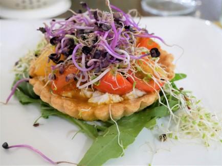 Crostatina di pomodori, ricotta di anacardi, limone e germogli